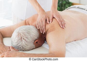Therapist massaging back of senior man
