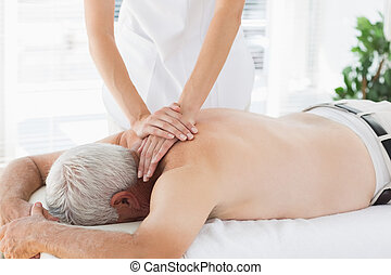 Therapist massaging back of senior patient - Massage...
