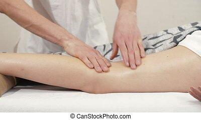 Therapist massaging female leg - Masseur doing massage on...