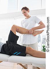 Therapist massaging leg of man