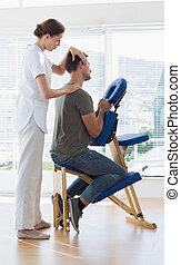 Therapist massaging man in hospital