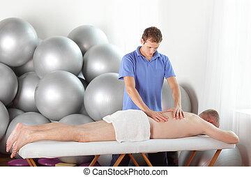 therapist massaging man - male therapist massaging middle...