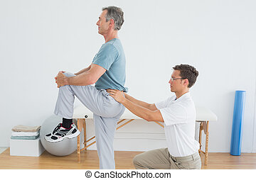 Therapist massaging mans lower back in gym hospital - Side ...