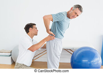 Therapist massaging mans lower back in gym hospital - Side...