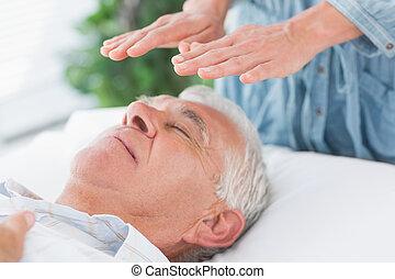 Therapist performing Reiki over senior man - Massage...
