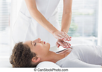 Female therapist performing Reiki over woman at health spa
