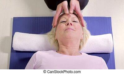 Therapist, reiki therapy to woman