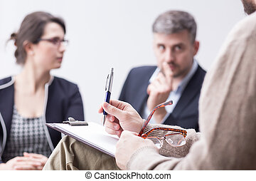 Therapist taking notes during marriage therapy session