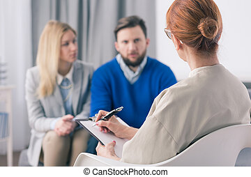 Therapist talking to a couple with problems