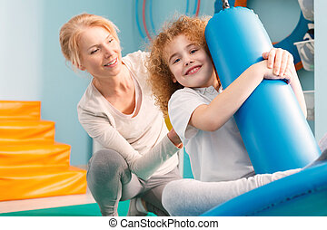 Therapist watching a boy on disc swing - Smiling therapist...