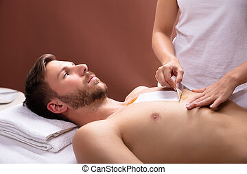 Therapist Waxing Man's Chest