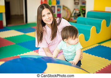 Portrait of a beautiful female therapist doing some early stimulation with a baby in a therapy center