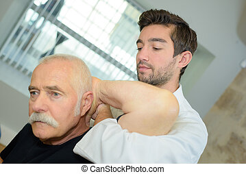Therapist working on man's shoulder