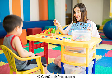 Cute Hispanic language therapist working with a kid in a special needs school