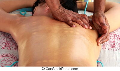 therapist's hands doing back massage on woman.