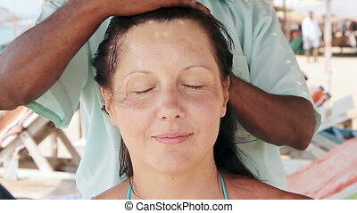 therapist's hands doing head massage on woman.