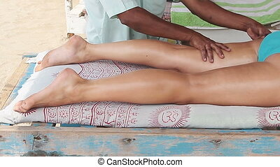 therapist's hands doing legs massage on woman.