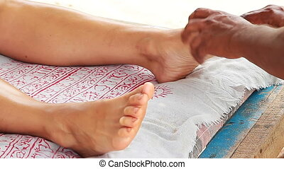 therapist's hands doing legs massage on woman.
