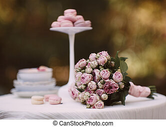 There are a bouquet and cookies on the table
