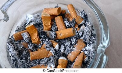 There are dozens of cigarette butts in the ashtray,