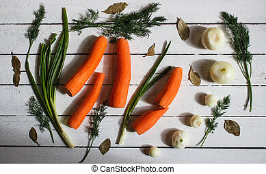some green, carrots and white onions on the table.