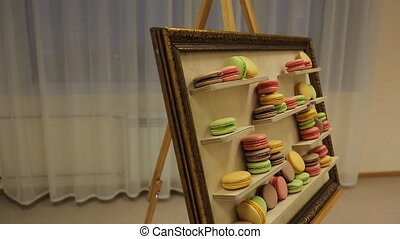 There is easel with macaroons served as picture of art.