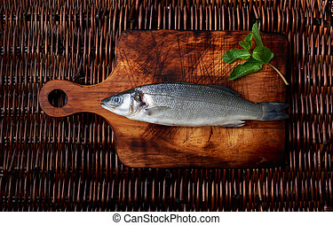 There is fresh fish on a wooden board - resh seabass on the ...