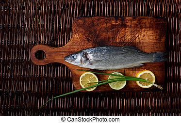 There is fresh fish on a wooden board - Sea bass lying on a ...