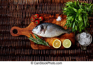 There is fresh fish on a wooden board - Sea bream on the ...