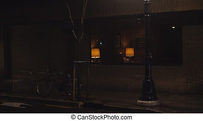 Empty street in night city in the rain. Dark scene with lonely bike and house entrance hall with dim light