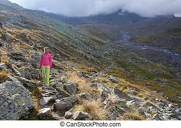 There is one girl walking in the mountains