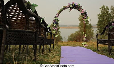 There is wedding arch with flowers on lake or river shore.