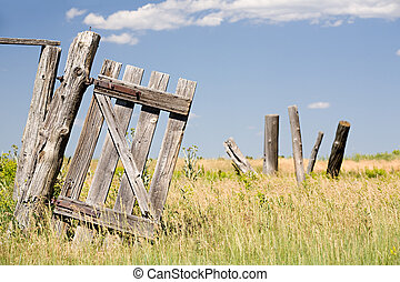 there once was a fence - old broken fence door hangs crooked...
