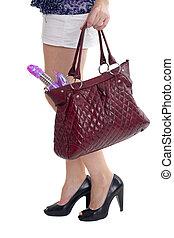 Ladies handbag in hands with the vibrator
