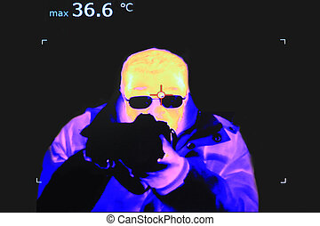 Thermal imaging - Thermal image of a man with the camera and...