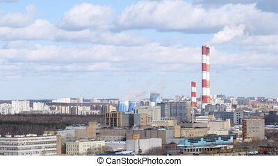 Thermal power plant stands near wood against city landscape