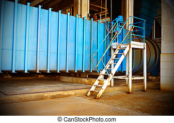 Thermal power plant workplace, large pipes and metal stairs.