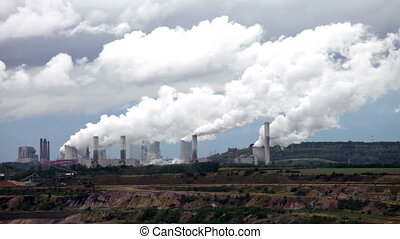 Thermal power station at open-cast coal mine under blue sky, smoking chimneys at background.