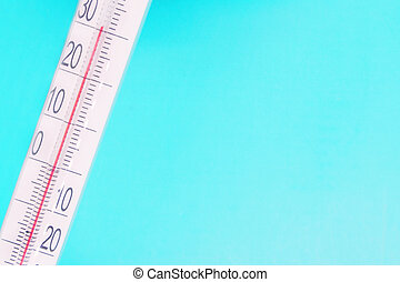 thermometer close-up on a blue background, high temperature on the thermometer scale, meteorological equipment, air temperature measurement