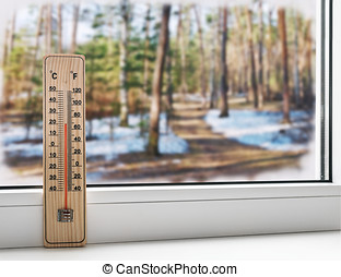Thermometer on a frozen window and cold weather in the spring st