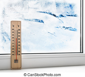 Thermometer on a frozen window and cold weather outside.