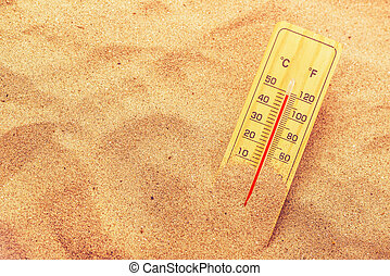Thermometer with celsius and farenheit scale on extremely warm beach sand showing record high temperatures