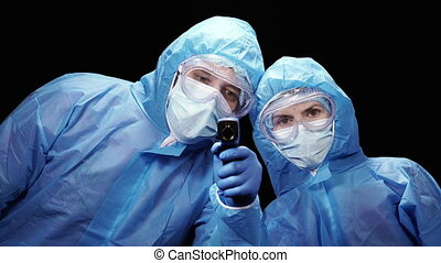 Thermometer. Virologists in antivirus suits measure ...