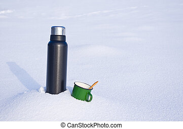 Thermos and mug in the snow