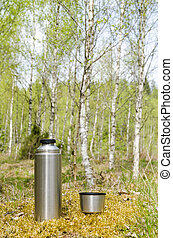 Thermos with beverages in a bright forest