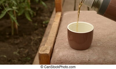 Thermos with poured tea in the garden - Brown thermos with...