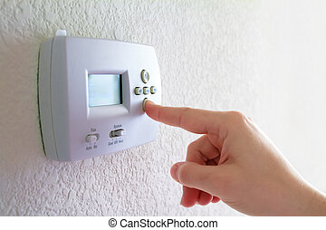 Thermostat and human hand - Thermostat on wall and human...