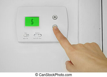 thermostat cost - Person adjusting a wall thermostat with...