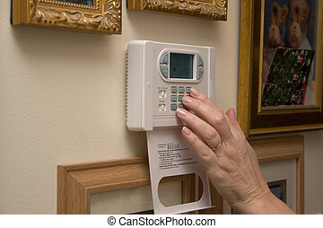 Female hand setting thermostat for comfort
