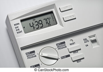 Programmable digital thermostat on a white wall.